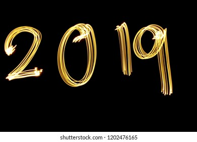 Lichtmalerei Fotografie, Langzeitbelichtung, goldmetallisches gelbes Licht, das die Ziffern '2019' vor einem schwarzen Hintergrund buchstabiert. Frohes neues Jahr Konzept