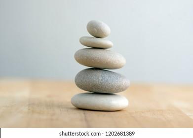 縞模様の灰色の白い背景の上の石のケアン、5つの石の塔、シンプルな落ち着いた石、シンプルな調和とバランス、岩禅の彫刻