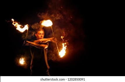 Feuershow. Feuertänzer tanzt mit. Nachtvorstellung. Dramatisches Porträt. Feuer und Rauch.