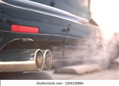 Nahaufnahme von rauchigen Doppelauspuffrohren aus einem startenden Dieselauto - Abgasskandal.