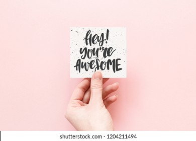 Minimal composition on a pink pastel background with girl's hand hold card with quote - Hey! You're awesome
