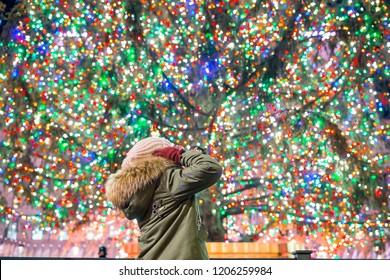 ニューヨークのロックフェラークリスマスツリーの背景に幸せな女の子。ロックフェラーセンターの美しいクリスマスツリー
