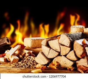 Gestapelte getrocknete Stämme vor einem brennenden Feuer in einer kalten Herbstnacht mit Holzpellets und Ziegeln