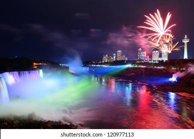 Die Niagarafälle werden nachts von bunten Lichtern mit Feuerwerk beleuchtet