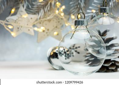 Weihnachtsglaskugeln, die gegen grauen Hintergrund mit verschwommenen Girlandenlichtern und Tannenzweigen hängen