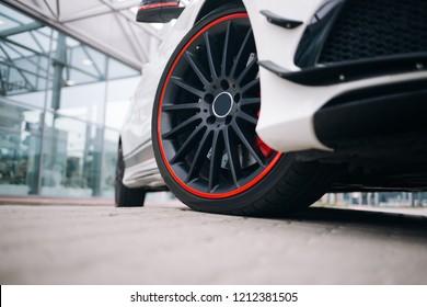 現代のスポーツキャットの前輪。白いスーパーカーの黒いリム