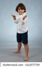 Small kid as spider man stand on gray studio background