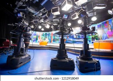 La cámara en el estudio está transmitiendo a periodistas leyendo noticias. Fondo borroso tiene tabla para reportero.