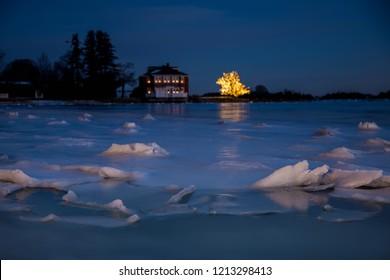 氷の湖のほとりの家の近くの木に輝くクリスマスライト。流氷のクローズアップと遠くの都市と夜の風景。セレクティブフォーカス。ぼやけた背景。あなたのための対処スペース