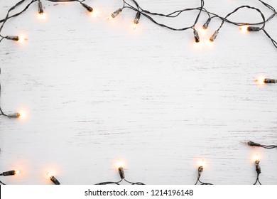 Weihnachtslichter Birnenrahmendekoration auf weißem Holz. Frohe Weihnachten und Neujahrsfeiertagshintergrund. Draufsicht