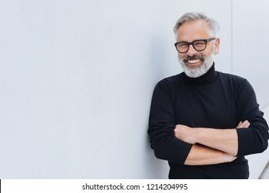 Entspannter, selbstbewusster älterer Mann mit Bart und Brille, der mit verschränkten Armen vor einer weißen Wand steht