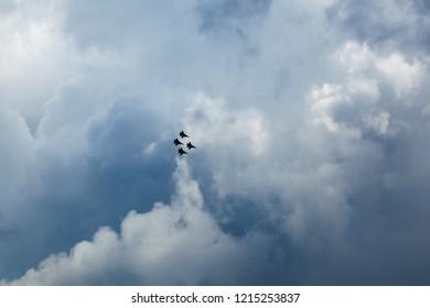 Siluetas de cuatro Su-30 SM, aviones de combate rusos en lo alto del cielo nublado azul