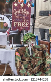 A memorial to the dead celebrating American Freedom and the military is displayed at a Day for the Dead festival. A sign saying bless American freedom is hung near skeleton dress in an army uniform.