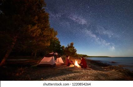 海岸での夜のキャンプ。星と青い水と森の背景の天の川でいっぱいの夕方の空の下でキャンプファイヤーでテントの前で休んでいる男性と女性のハイカー。アウトドアライフスタイルのコンセプト