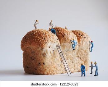 全粒パンの背景、チームの仕事の概念に取り組んでいる労働者の人の多くのミニチュアの人々を閉じます。