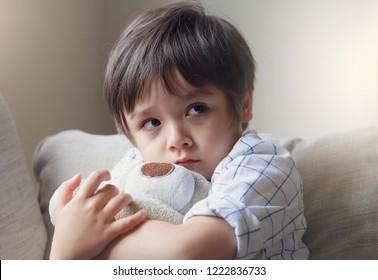 Dramatisches Porträt des kleinen Jungen, der auf Sofa sitzt und Teddybär mit ängstlichem Gesicht kuschelt, unglückliches Kind, das allein sitzt und mit besorgniserregendem Gesicht heraus schaut, Kleinkindjunge auf Eckbestrafungssitzung.