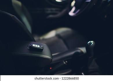 ワイヤレスキーイグニッションの車内のクローズアップ。エンジンキーを起動します。黒の穴あきレザーインテリアの車のキーリモコン。車のディテール。キーがクローズアップ。