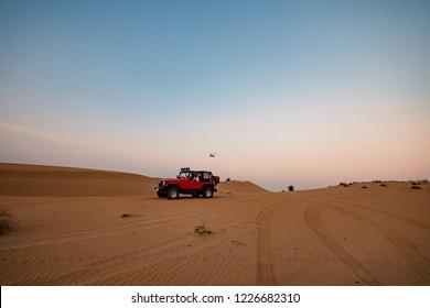 Mann, der roten Jeep in der Wüste in der Dämmerung fährt.