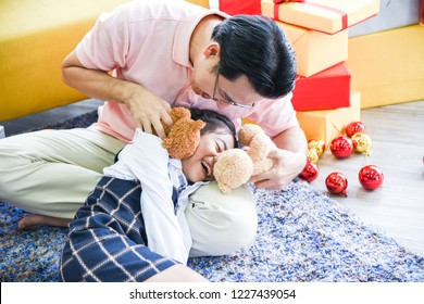 The daughter lies on her father's lap. Dad and daughter are playing teddy bear together very fun and happy on Christmas day.Concept Christmas Day, Family Day, Christmas Eve , Happy New Year