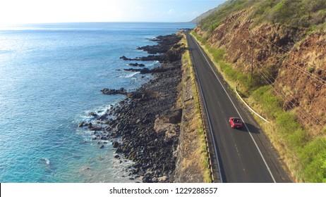 AERIAL: Rotes Cabrio, das entlang der malerischen Küstenstraße über den großen Klippen des Ozeans fährt und Meerwasser in Felsen spritzt. Glückliches junges Paar in den Sommerferien, die am Meer reisen