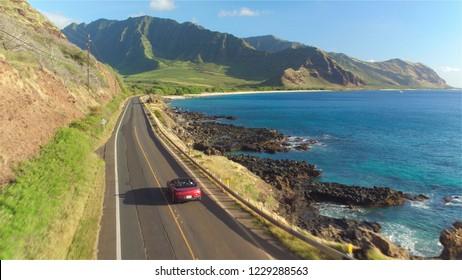 AERIAL: Rotes Cabrio, das entlang der malerischen Küstenstraße über dem dramatischen felsigen Ufer in Richtung wunderschöner Vulkanberge fährt. Glückliches junges Paar in den Sommerferien, die am Meer reisen
