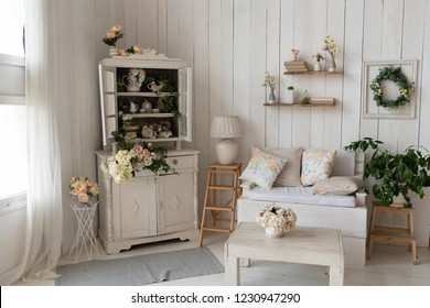 sofa stands in the interior light studio room near the romantic fireplace and windows decorated with spring flowers, wreath, mirror, old decor