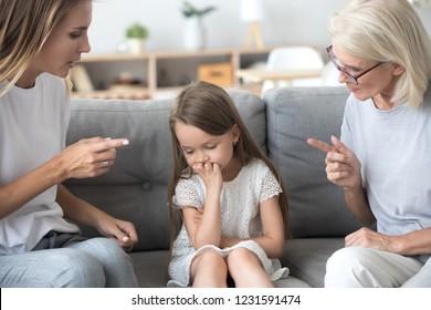 Madre enojada y abuela regañando disgustando a una niña molesta, una madre joven y una abuela estrictas hablando con un niño que reprendió disciplina exigente, un concepto de educación de tres generaciones