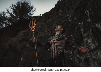 A fury man in armor and with a trident in his hands against the background of rocks.