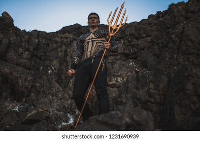 A young man in armor with a trident in his hands against the background of rocks and sky.
