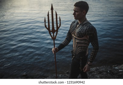 A young man in armor with a trident in his hands against the background of water.