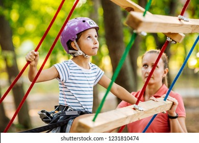 female instructor helps the child on the rope road in the training camp.