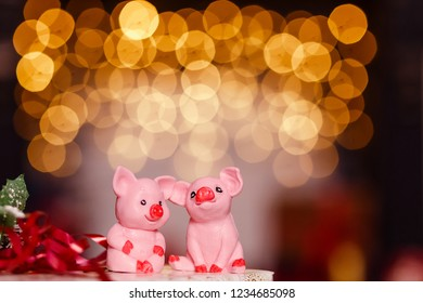 two pink pig figurines at the background lamps garlands. the symbol of the new year, the year of the pig