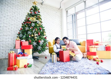 Dad and daughter opening a gift box on Christmas Day. Daughter is excited, the gift is in the box very much. She is happy to receive gifts from her father. Concept Christmas Day, Family Day