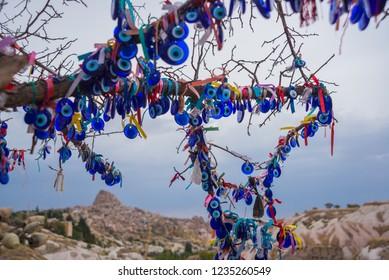 Capadocia, Turquía, Uchisar: Árbol colgando amuletos de Nazar, un objeto especial en forma de ojo que protege contra el mal de ojo
