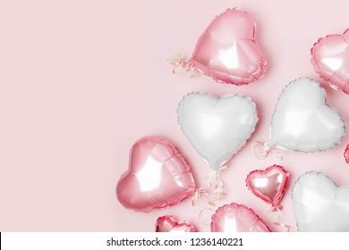 ハート形のパステルピンクの背景に箔の気球。愛の概念。休日のお祝い。バレンタインデーまたは結婚式/バチェロレットパーティーの装飾。金属風船