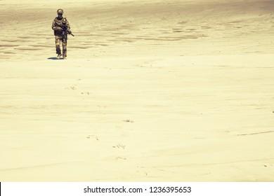 Soldado del ejército en uniforme, con carabina de servicio en manos caminando a través de arenas calientes desaturadas, tono sepia. Intervención militar o campaña en la región del Medio Oriente, conflicto armado en el área del desierto