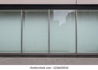 大きな窓と名前の場所があるブティックストアフロントのショップ