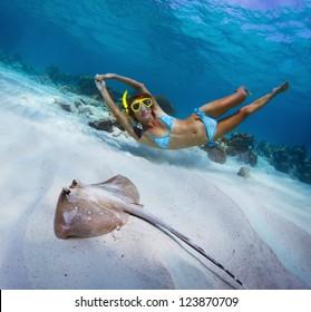 砂浜の海底を泳ぐ女性の水中撮影