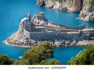 Porto Venere (Portovenere), Liguria, Italia: hermosa vista aérea aérea de la Iglesia de San Pedro (Chiesa di San Pietro) desde la isla de Palmaria cerca de Cinque Terre con la gruta de Byron