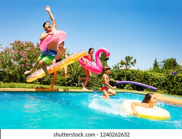 Happy friends jumping in pool on the vacations