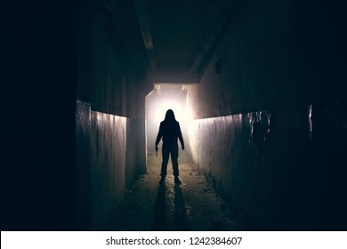 Silhouette of maniac with knife in hand in long dark creepy corridor, horror psycho maniac or serial killer concept, toned
