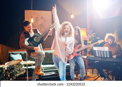 ギグの準備をしているジャズバンド。フォアグラウンドの女性がベースギター、クラビエ、アコースティックギターを演奏しながら歌っています。ホームミュージックスタジオのインテリア。
