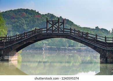 穏やかな運河に架かる中国の橋。赤壁市にて。木製で作られた橋。中国湖北省の3つの王国の戦場にある古代の橋。