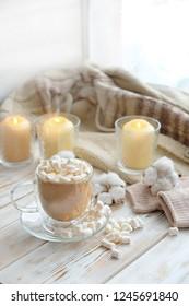 acogedor invierno bodegón. café, malvavisco, velas. composición festiva de invierno, concepto de vacaciones de Navidad y año nuevo. cacao y malvavisco. clima suéter, hogar acogedor, fondo de temporada de invierno