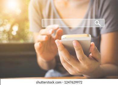 女性はスマートフォンを使って興味のあるものを見つけます。インターネットネットワーキングの概念に関する情報データの検索