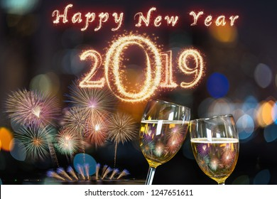新年あけましておめでとうございます2019は、お祝い、パーティー、新年あけましておめでとうございますのコンセプトで祝うために街並みのぼやけた写真の上に2つのビールジョッキまたはグラスでチャリンという音にスパークル花火で書かれました