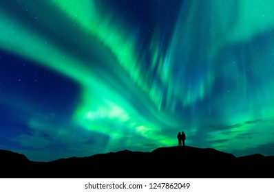 Aurora Borealis mit Silhouette lieben romantisches Paar auf dem Berg. Flitterwochen-Reisekonzept