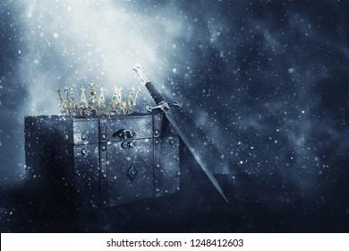 mysterieus en magisch beeld van oude kroon, houten kist en zwaard over gotische zwarte achtergrond. Middeleeuwse periode concept