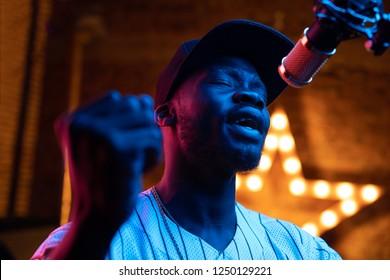 Man met baard en snorren in honkbalpet en t-shirt zingen in de microfoon. Roze en blauw neonlicht, ster op achtergrond