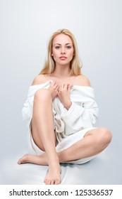 バスローブの床に座って美しい金髪の女性